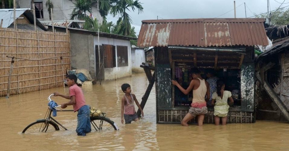 8.out.2015 - Jovens compram itens básicos em uma loja improvisada após chuva torrencial inundar Dimapur, em Nagaland, na Índia