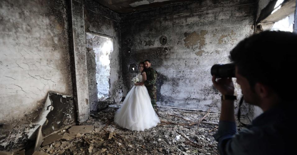 6.fev.2016 - Os recém-casados Nada Merhi, 18, e Hassan Youssef, 27, recebem instruções do fotógrafo Jafar Meray, em Homs, na Síria. O casal decidiu fazer o resgitro do casamento em meio as ruínas da cidade devastada pela guerra, para mostrar que mesmo no mais hostil dos ambientes, a vida é mais forte que a morte