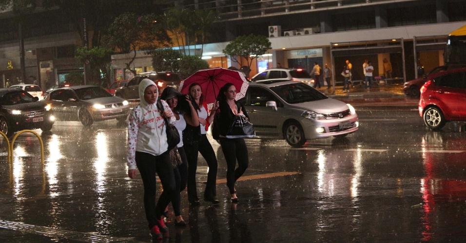 27.set.2015 - Pedestre se protege da chuva na região da avenida Paulista em São Paulo (SP), neste domingo (27)