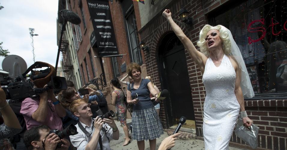 26.jun.2015 - A drag queen canadense Carlotta Gurl celebra a oficialização do casamento gay nos Estados Unidos na calçada em frente ao prédio Stonewall Inn, no bairro de Greenwich Village, em Nova York. O edifício é uma referência para a comunidade gay da cidade. Carlotta se vestiu de noiva após a Suprema Corte, a mais alta instância da Justiça norte-americana, decidir que casais homossexuais devem ter os mesmos direitos que os casais heterossexuais. Na prática, está legalizado o casamento civil gay nos Estados Unidos