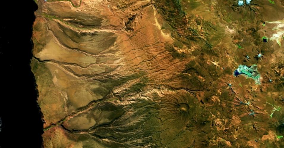 31.jul.2015 - O deserto de Atacama, localizado no norte do Chile, é o local mais seco da Terra, apesar de estar bem ao lado do oceano Pacífico. Em média, apenas alguns milímetros de chuva atingem a paisagem árida anualmente. A fria Corrente de Humboldt mantém a umidade da costa norte até ao oeste, enquanto a Cordilheira dos Andes bloqueia a precipitação a partir do leste. A imagem feita pelo telescópio Proba-V da ESA (Agência Espacial Europeia) mostra a costa e os rios secos do vale do Atacama. A área azul à direita é o Salar de Surire, uma planície de sal que contém lagos com ninhos de flamingos. Lançada em 7 de maio de 2013, o Proba-V é um tem a missão de mapear a superfície e o crescimento da vegetação ao longo de todo o planeta a cada dois dias