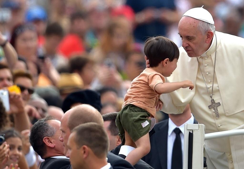 2.ago.2015 - Papa Francisco abençoa criança ao chegar à praça de São Pedro para a audiência semanal, no Vaticano
