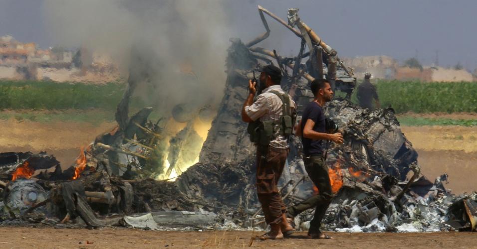 1º.ago.2016 - Homens inspecionam os destroços de um helicóptero russo que foi derrubado por forças rebeldes no norte da Síria. Cinco soldados morreram, de acordo com autoridades russas. Após o ataque, subiu para 18 o número de militares mortos na Síria desde a intervenção russa, em 30 de setembro de 2015