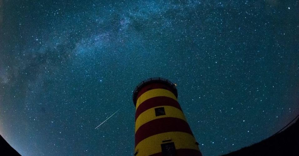 13.ago.2015 - Meteoros riscam o céu próximo a um farol em Pilsum, noroeste da Alemanha. A chuva de meteoros Perseidas ocorre anualmente e tem este nome por ser avistada da Terra próximo da constelação de Perseu