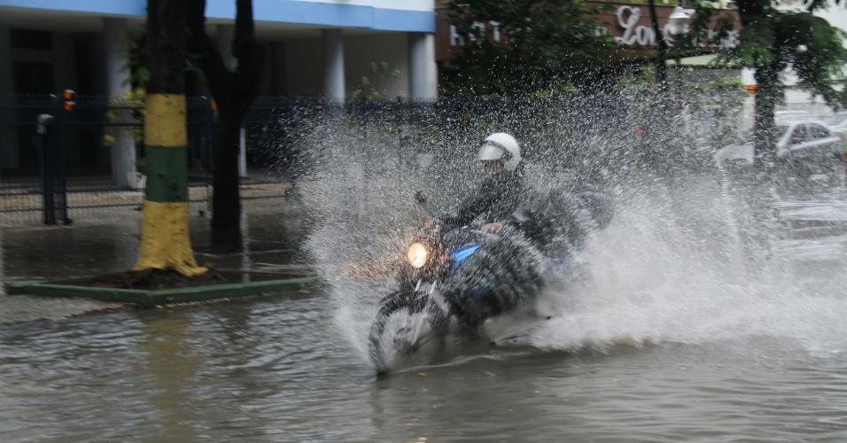 16.mar.2016 - Motoqueiro tem dificuldade de dirigir após chuva alagar a rua do Catete, na zona sul do Rio de Janeiro. Com o forte temporal, a cidade entrou em estágio de atenção e um alerta prévio de possibilidade de chuva forte foi emitido em 103 comunidades