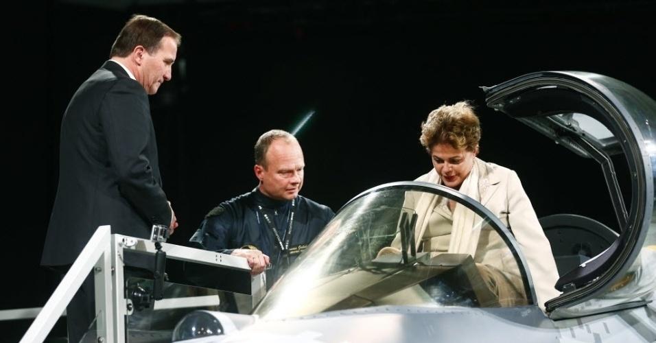 19.out.2015 - O piloto de testes Jonas Jakobson (ao centro) mostra para a presidente Dilma Rousseff e para o primeiro-ministro da Suécia, Stephen Lofven (à esq.) um novo avião caça JAS 39E Gripen, durante visita da líder brasileira em Linkoping, na Suécia