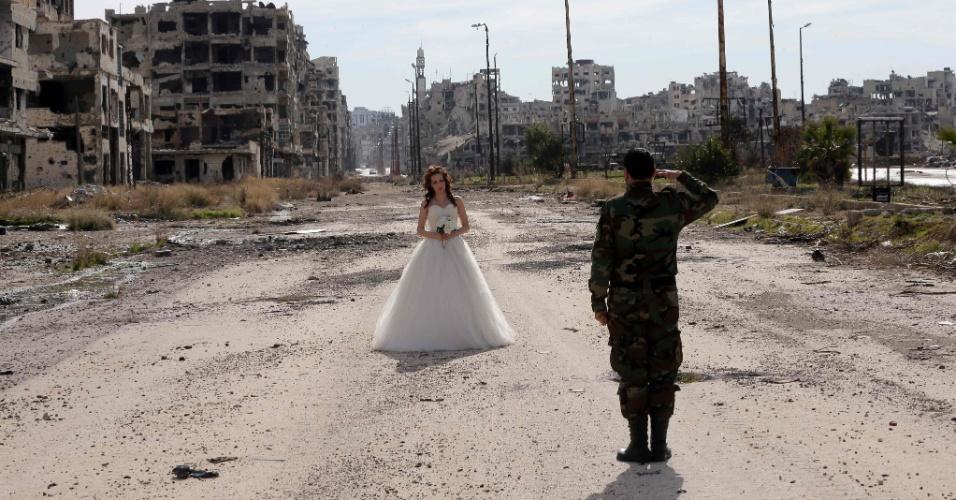 6.fev,2016 - Os recém-casados Nada Merhi, 18, e Hassan Youssef, 27, recebem instruções do fotógrafo Jafar Meray, em Homs, na Síria. A cidade era anteriormente um reduto rebelde - apelidado de capital da revolução, quando a luta começou em 2011 - até que as forças pró-governo a tomaram de de volta em 2014.