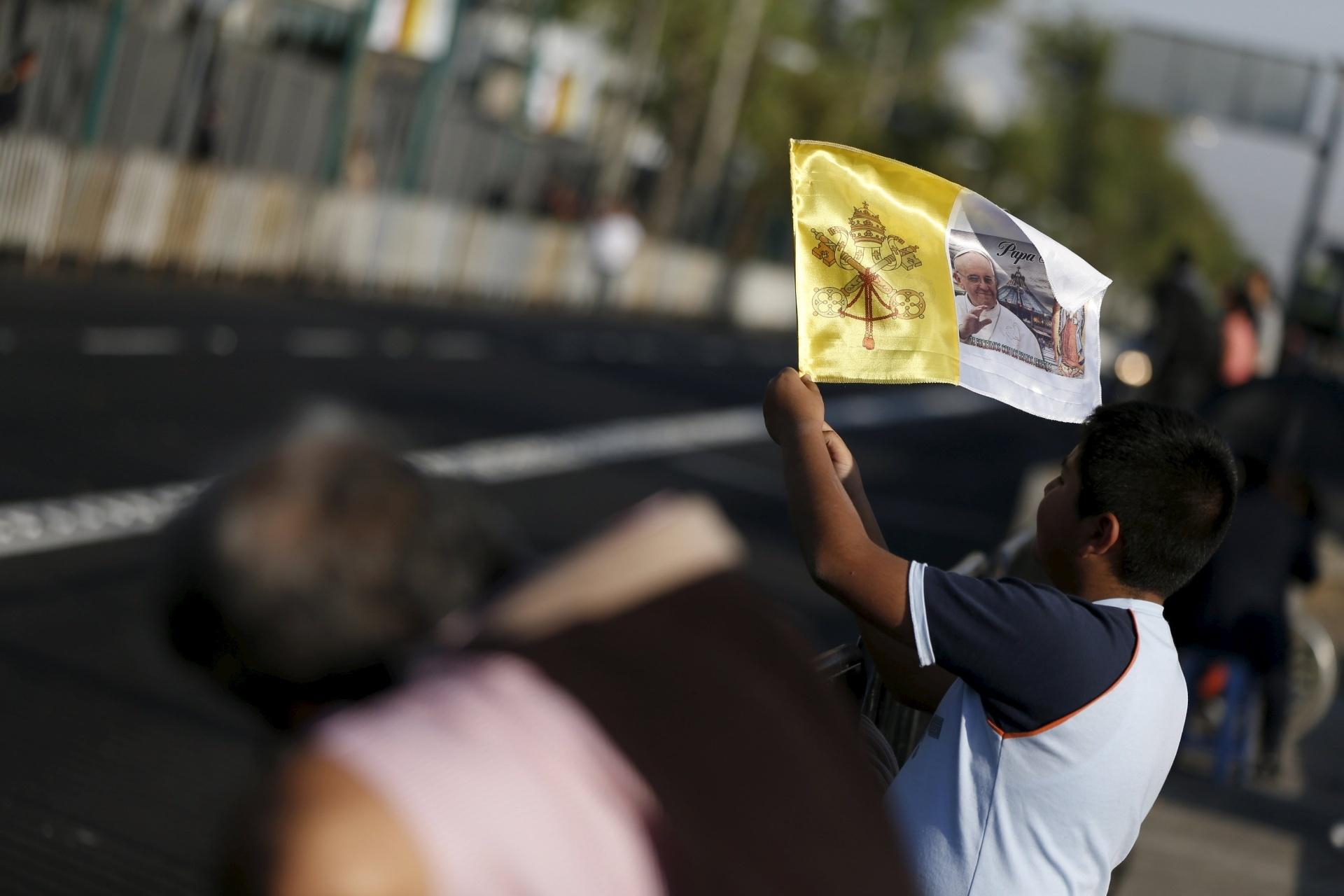 13.fev.2016 - Garoto mexicano espera pela passagem de carro do papa Francisco na Cidade do México segurando bandeira com as cores do Vaticano e uma foto do líder católico. Em sua visita de cinco dias ao país, o pontífice deve abordar assuntos como violência, pobreza, migração e corrupção