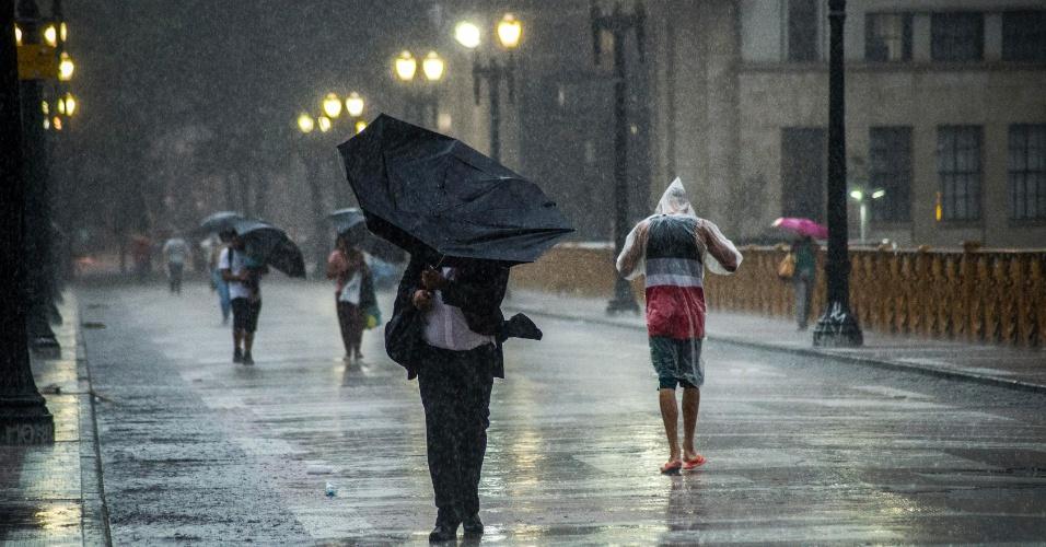 27.jan.2016 - Pedestres enfrentam temporal no viaduto Santa Ifigênia, na região central de São Paulo, nas primeiras horas da tarde. Estava tão escuro que as luzes da cidade foram acesas
