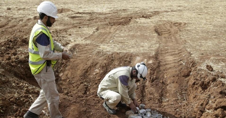 8.out.2015 - Funcionários da Defesa Civil descartam explosivos detonados, disparados pela Força Aérea Russa, em Maasran, na Síria. Segundo o governo sírio, os bombardeios russos permitiram enfraquecer os radicais do Estado Islâmico