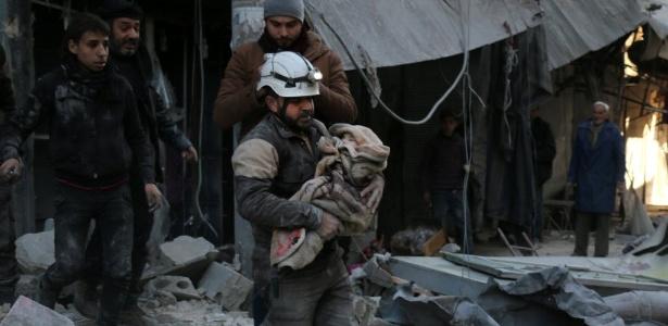 Membro da Defesa Civil síria caminha sobre escombros enquanto carrega criança envolta em um cobertor, em Aleppo, na Síria