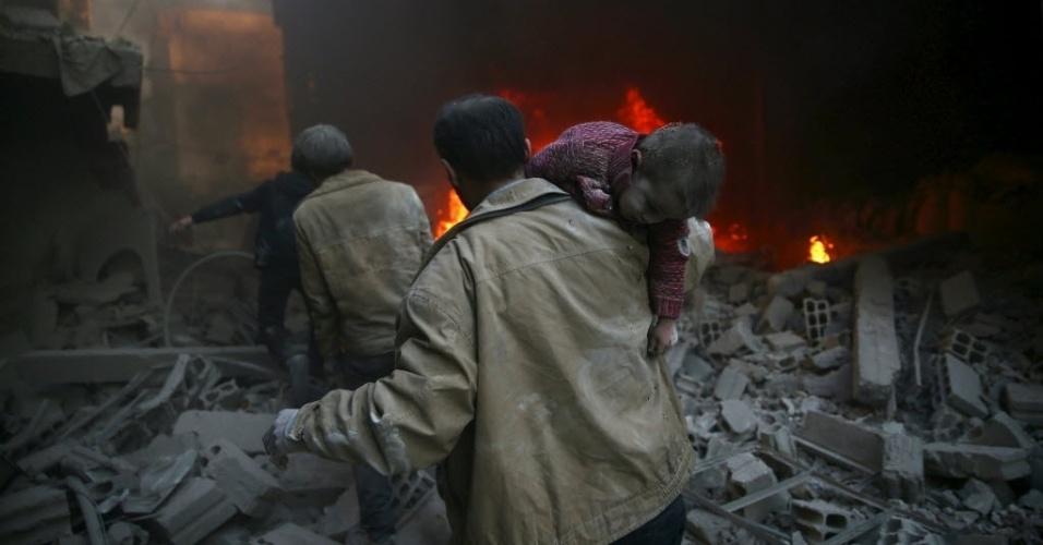 30.dez.2015 - Homem carrega criança ferida de local destruído por um ataque a bomba de forças leais ao presidente sírio, Bashar al-Assad, na cidade de Douma, no leste de Ghouta, em Damasco, Síria