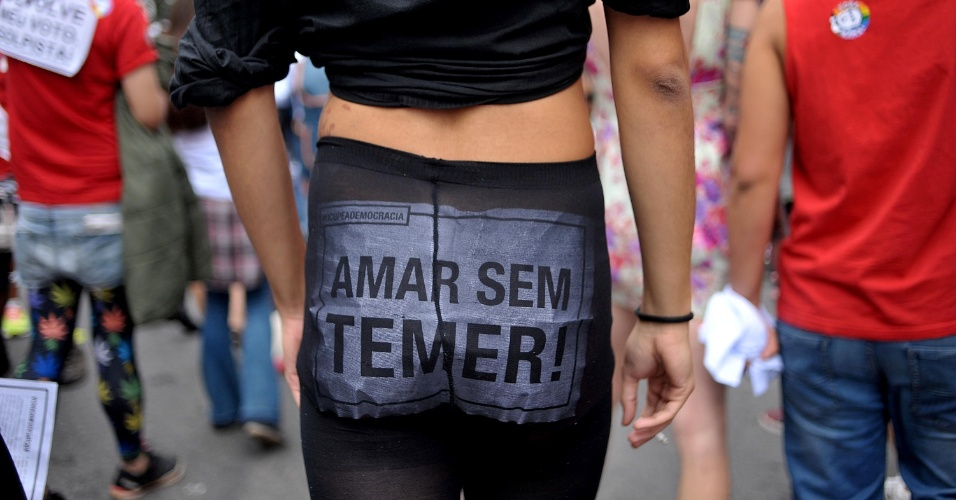 29.mai.2016 - Participante da Parada Gay, em São Paulo, caminha com cartaz em protesto ao governo interino de Michel Temer, neste domingo. A parada deste ano foi marcado por gritos de