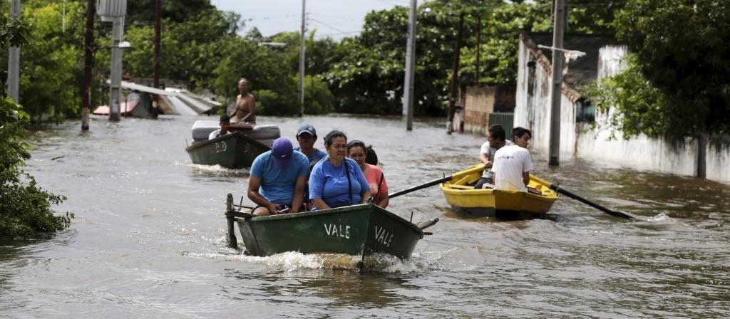 27.dez.2015 - Pessoas usam barco para transitar em rua alagada de Assunção, no Paraguai. As inundações generalizadas obrigaram mais de 100 mil pessoas a deixarem suas casas na região fronteiriça entre Paraguai, Argentina, Uruguai e Brasil, após dias de chuvas torrenciais causadas pelo fenômeno El Niño