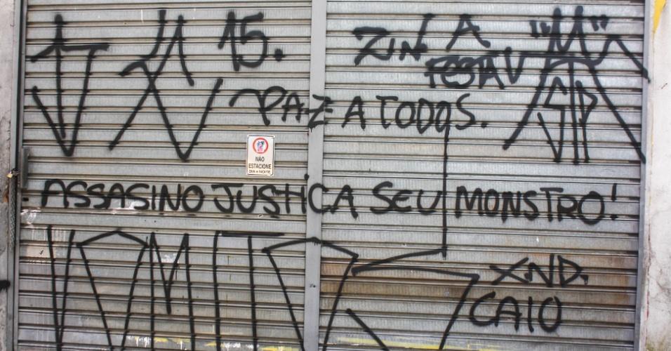 02.out.2015 - Porta de garagem ao lado do terreno onde o pintor Jorge Luis de Morais Oliveira, de 41 anos, teria enterrado suas vitimas no Jabaquara, zona sul de São Paulo, amanhece pichada.