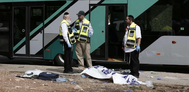 Forças de segurança israelenses conversam ao lado de corpo após ataque a tiros contra um ônibus em um assentamento judaico próximo ao bairro palestino de Jabal Mukaber, em Jerusalém Oriental