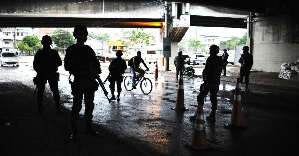 19.jun.2015 - Militares das Forças Armadas atuam em posto de bloqueio sob viaduto na entrada da comunidade Vila dos Pinheiros, no complexo da Maré, zona norte do Rio de Janeiro. A Força de Pacificação vai deixar as favelas no dia 30 de junho, após 15 meses de ocupação