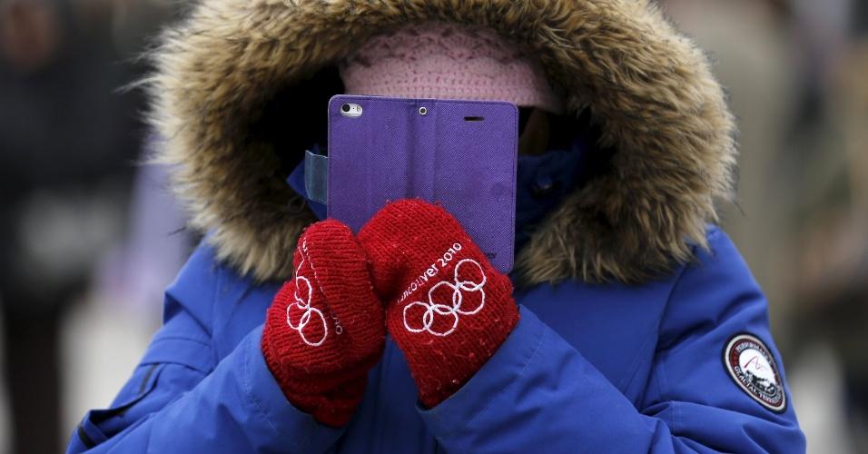 3.abr.2016 - Será que está frio no Canadá? Em plena primavera de Toronto, uma mulher bastante agasalhada fica completamente coberta por casacos enquanto tira foto com seu celular da parada anual que celebra o Dia da Independência da Grécia