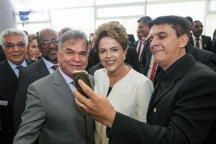 24.nov.2015 - Dilma Rousseff tira selfie com populares em evento realizado em Brasília. Presidente participou de cerimônia de anúncio dos critérios de outorgas de radiodifusão AM para FM