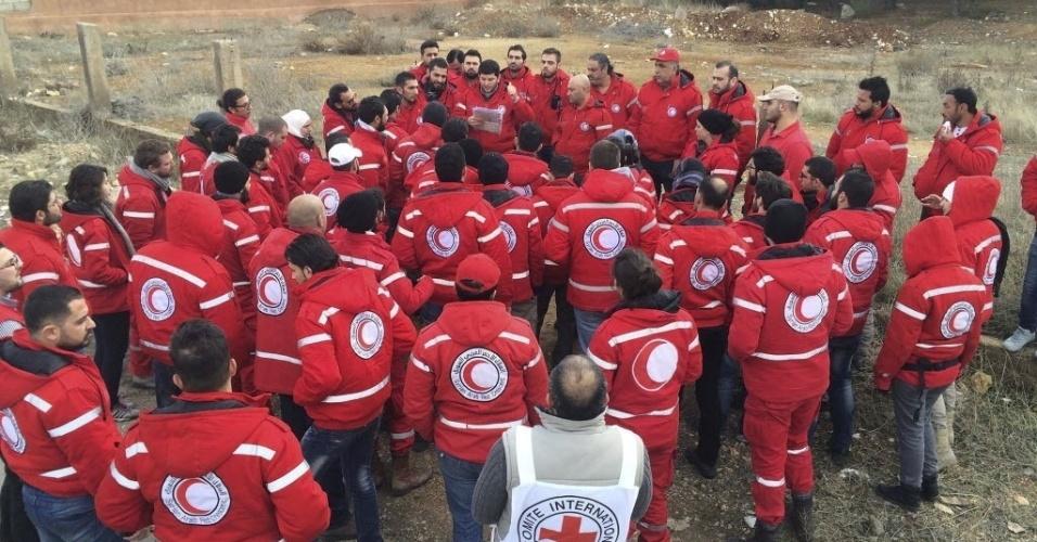 14.jan.2016 - Membros do comboio da Cruz Vermelha recebem instruções antes de saírem para levar ajuda humanitária à cidade sitiada de Madaya, na Síria. O grupo deve levar alimentos e medicações ao local