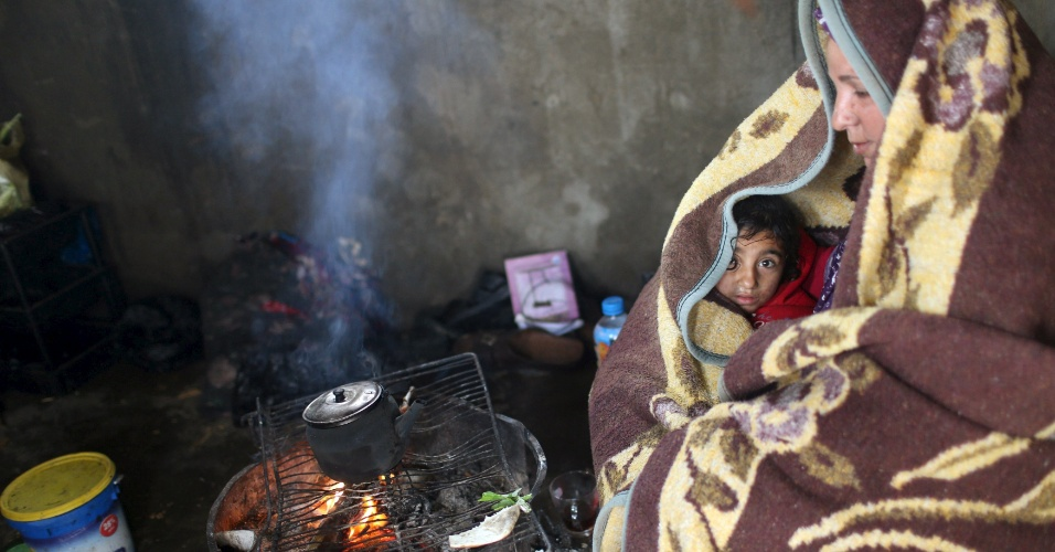 25.jan.2016 - Uma mãe palestina e sua filha se protegem do frio durante uma tempestade de inverno em Khan Younis, na parte sul da Faixa de Gaza. Além do frio, a região está sendo seriamente afetada por chuvas que causam alagações