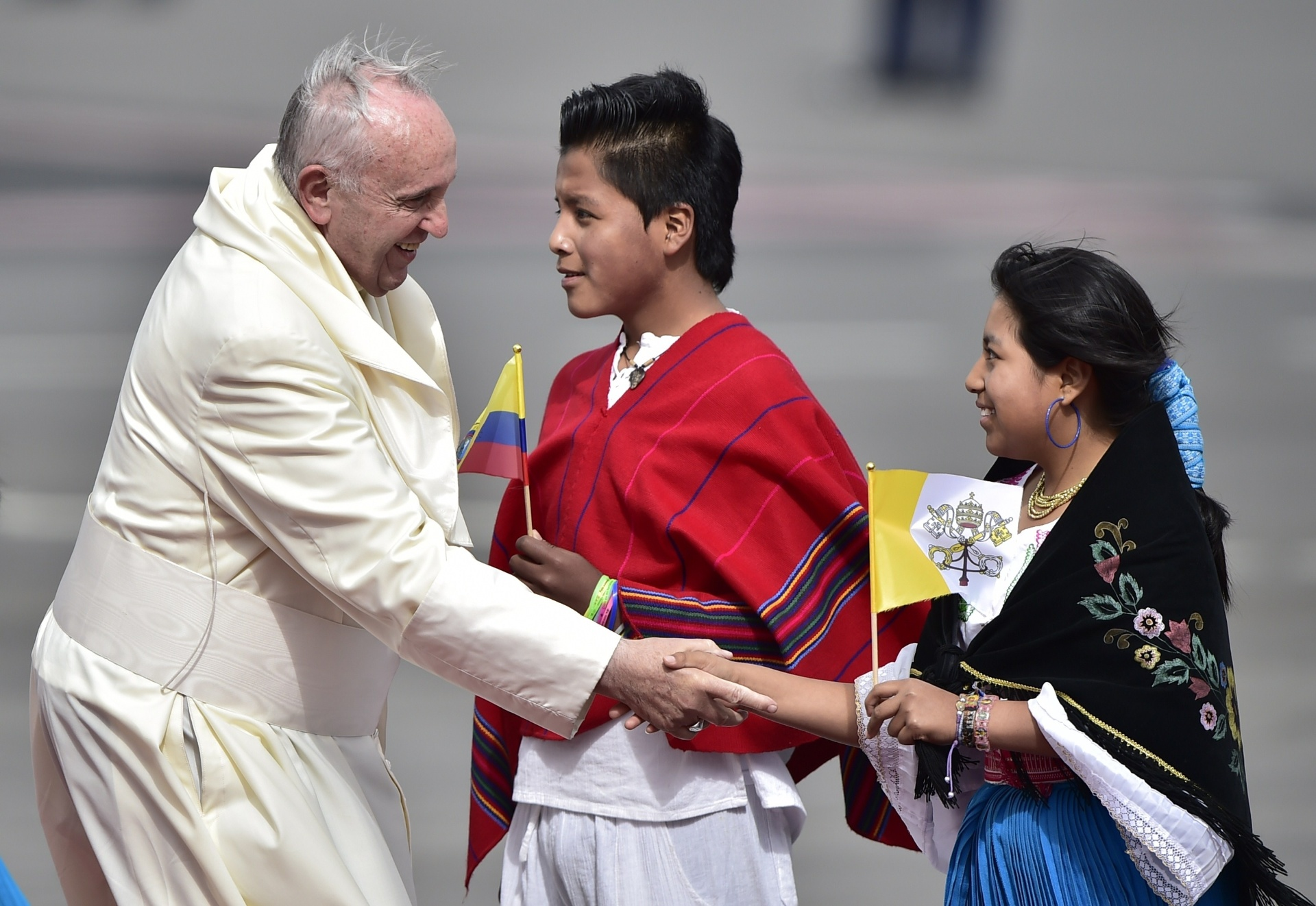 5.jul.2015 - Papa Francisco é cumprimentado por jovens equatorianos, vestidos com trajes típicos do país, no Aeroporto Internacional Mariscal Sucre, em Quito