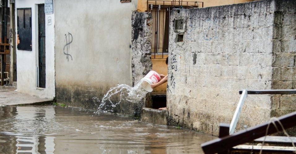 8.set.2015 - Morador retira água que entrou em sua casa na rua Agreste de Itabaiana, na zona leste de São Paulo