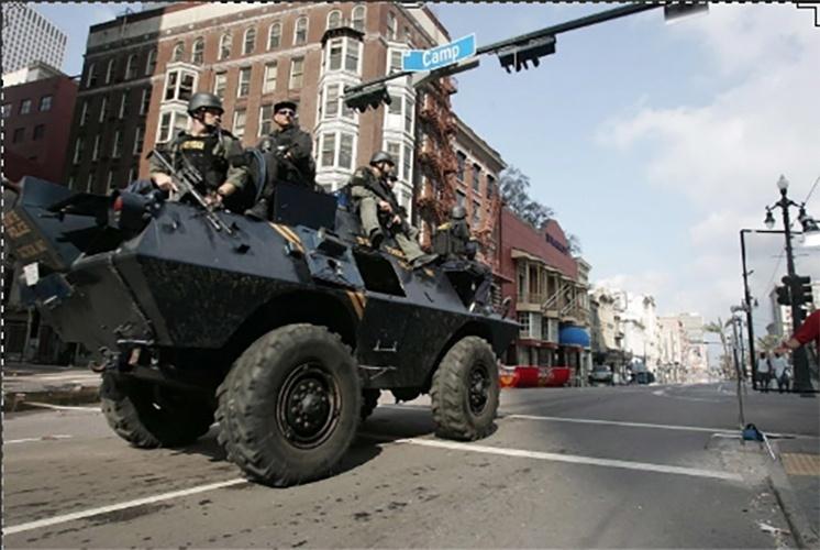 2005: Veículo blindado patrulha rua de Nova Orleans, Louisiana (EUA), após a passagem do furacão Katrina, que varreu edifícios, alagou quase totalmente a cidade e causou mais de 1.800 mortes