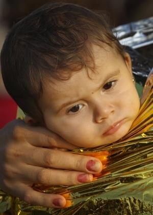 Criança síria é coberta com manta térmica ao chegar a Kos, na Grécia
