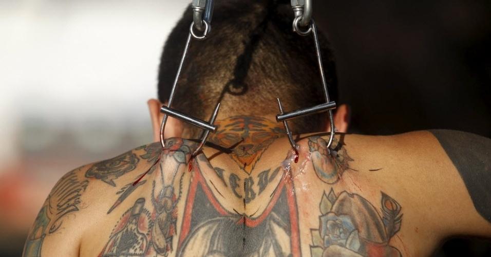 14.set.2015 - Visitante é suspenso por ganchos durante convenção de tatuagem em Cali, na Colômbia