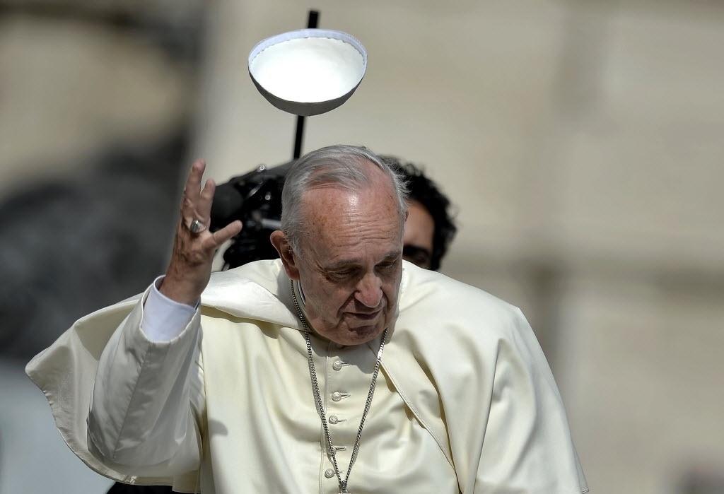 24.jun.2015 - Rajada de vento faz com que o solidéu do papa Francisco saia voando durante sua chegada em carro aberto para a audiência semanal na praça São Pedro, no Vaticano