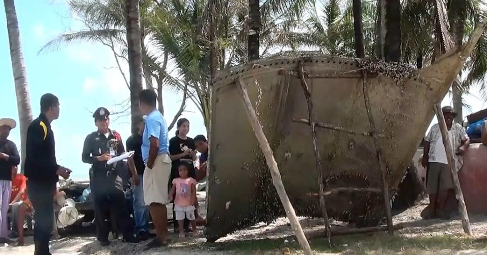24.jan.2016 - Em foto do último sábado (23), uma suposta parte de avião é inspecionada por policiais e cidadãos em um vilarejo do sul da Tailândia. Peça levanta questões sobre misteriosa queda de avião da Malaysia Airlines, até hoje não encontrado