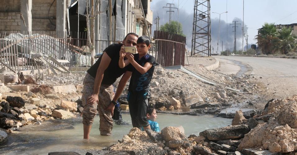 20;ago.2016 - Moradores do bairro de Sheikh Saeed, em Aleppo, na Síria, aproveitam que cano de água estourou e transformam área destruída por bombardeios em área de recreação. A região é dominada por rebeldes