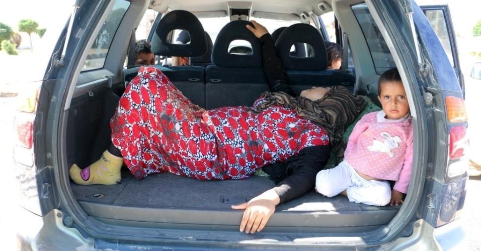 25.jun.2015 - Vítima de combatentes do Estado Islâmico aguarda para cruzar a fronteira para a Turquia, na cidade síria de Tel Abyad. Segundo a televisão estatal síria, os jihadistas atacaram a cidade fronteiriça predominantemente curda de Kobani