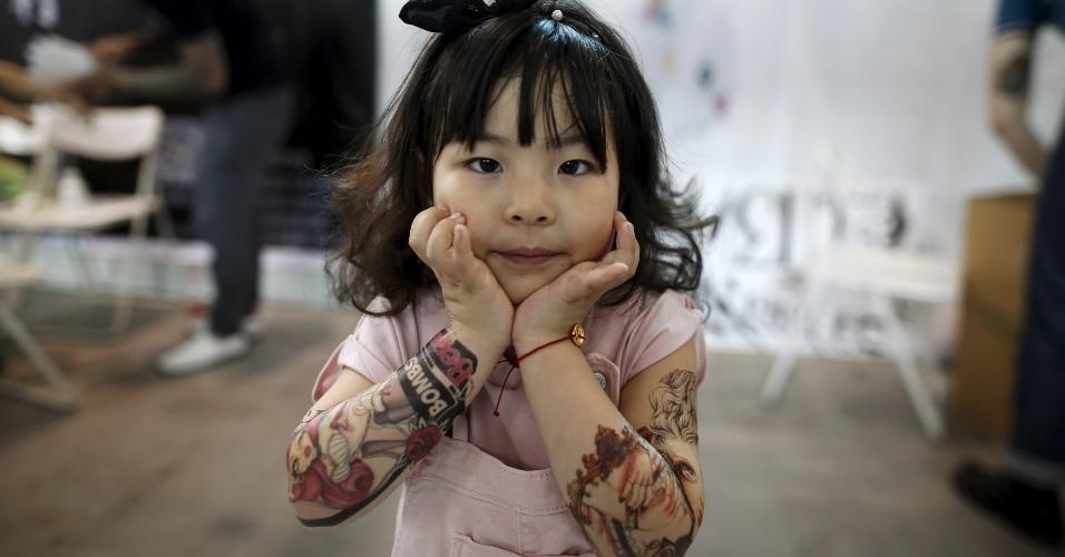 23.abr.2016 - Candy Wang, 4, mostra suas tatuagens feitas de adesivos no Festival Internacional de Artes de Tatuagens em Xangai, na China
