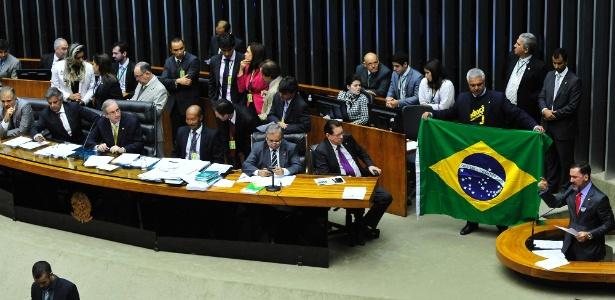 Observado por Eduardo Cunha (ao centro), deputado a favor da redução da maioridade estende bandeira do Brasil