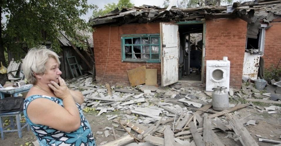 16.ago.2015 - Moradora observa casa que foi danificada em bombardeio nos arredores de Donetsk, no leste da Ucrânia. Mais de 845 militares ucranianos figuram como desaparecidos em combate após 16 meses de conflito armado no leste do país, informou neste domingo Irina Geraschenko, membro da delegação de Kiev no processo de paz de Minsk