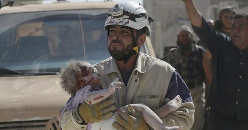20.out.2015 - Membro da Defesa Civil carrega um bebê ferido que sobreviveu após ficar soterrado em um local atingido por um ataque aéreo de forças leais ao ditador sírio Bashar Assad, na cidade de Marshamsha, sul da Síria