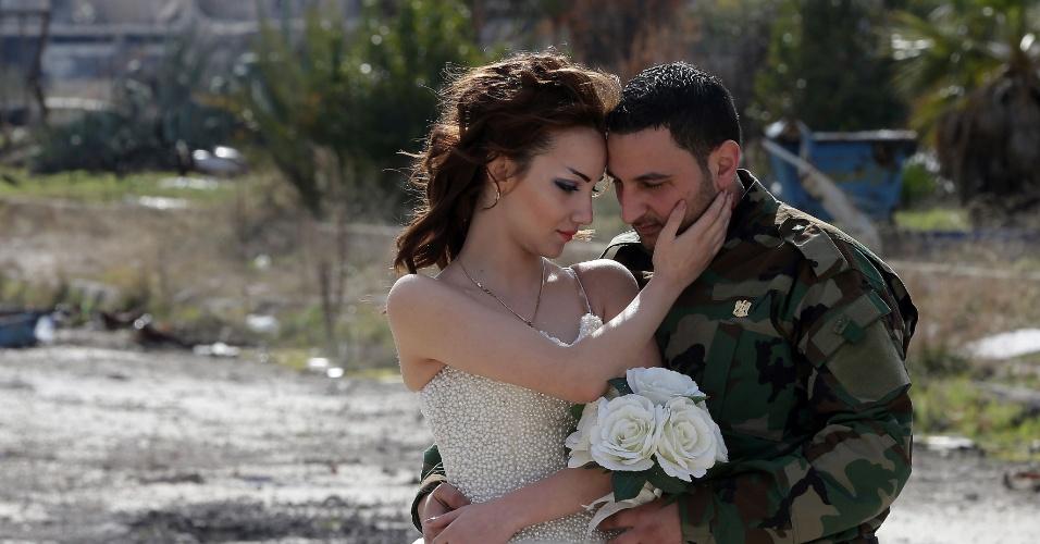 6.fev.2016 - Os recém-casados Nada Merhi, 18, e Hassan Youssef, 27, recebem instruções do fotógrafo de casamento para registrar imagens em meio a prédios destruídos pela guerra em Homs, na Síria. O fotógrafo registra imagens dos noivos nestes locais para mostrar que a vida é mais forte que a morte