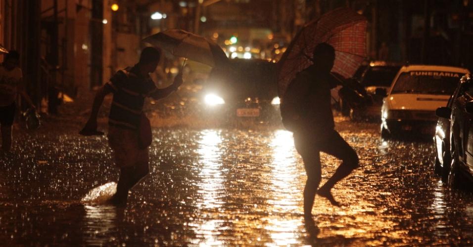21.fev.2016 - Homens tentam escapar alagamento próximo à rua dos Inválidos, na Lapa, centro do Rio de Janeiro, durante chuva na noite deste domingo