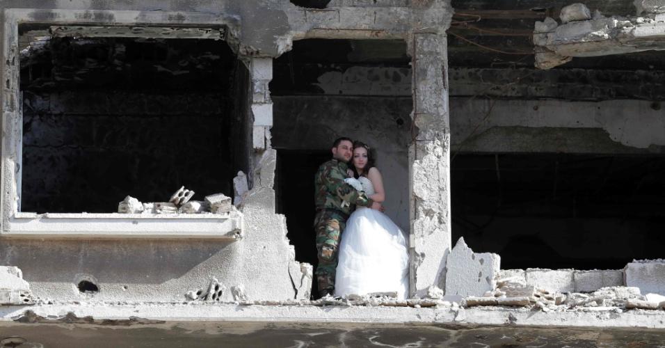 6.fev.2016 - Os recém-casados Nada Merhi, 18, e Hassan Youssef, 27, recebem instruções do fotógrafo Jafar Meray, em Homs, na Síria. A cidade era anteriormente um reduto rebelde - apelidado de capital da revolução, quando a luta começou em 2011 - até que as forças pró-governo a tomaram de de volta em 2014.