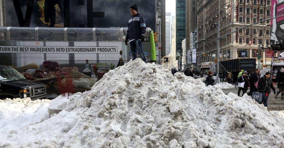 25.jan.2016 - Criança brinca no alto de um grande monte de neve acumulada na Time Square, em NY, após a nevasca que atingiu os EUA