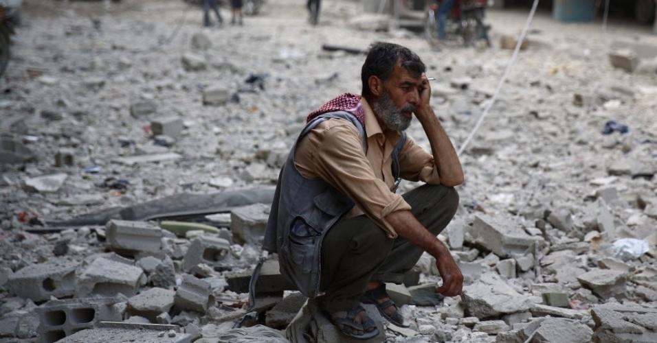 30.ago.2015 - Sírio senta no meio dos escombros de prédios destruídos por ataques aéreos das forças do ditador Bashar Assad, em área controlada pelos rebeldes, em Douma, a leste da capital Damasco. Mais de 240 mil pessoas foram mortas desde que o conflito da Síria começou em março de 2011, e metade da população do país tem sido deslocada pela guerra