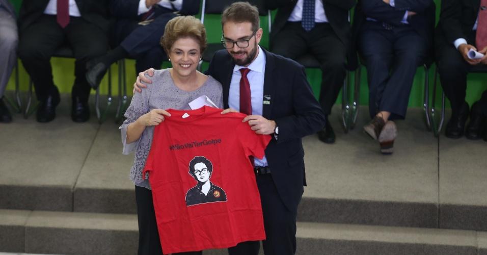 22.mar.2016 - A presidente Dilma Rousseff posa para foto segurando uma camiseta vermelha com estampa de seu rosto e a frase