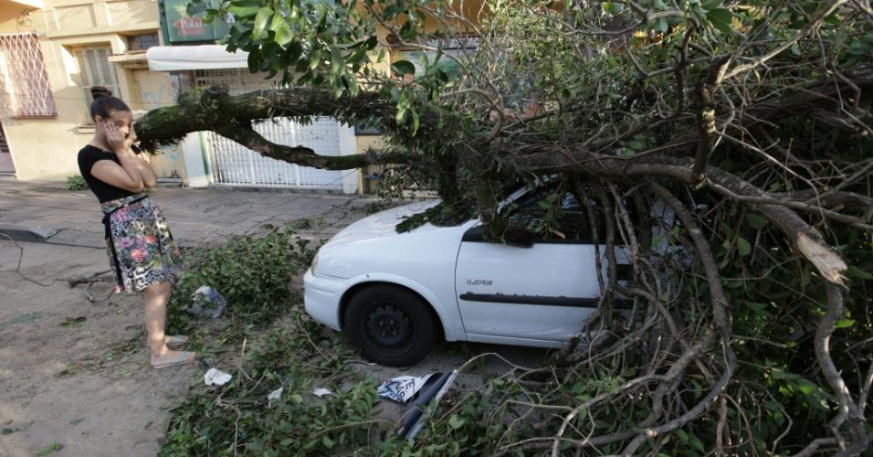 30.jan.2016 -Carro é atingido por uma árvore durante temporal el Porto Alegre (RS), na noite de sexta-feira (29). O temporal provocou falhas no abastecimento de energia elétrica e deixou sem luz pelo menos 328 mil clientes de Porto Alegre e da região retropolitana