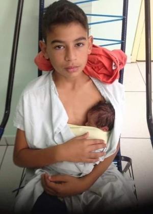 A imagem do menino segurando o irmãozinho recém-nascido no colo foi publicada na rede social