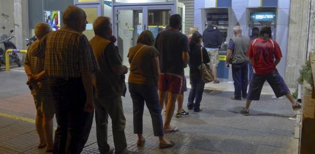 Clientes fazem fila para sacar dinheiro em um caixa eletrônico em Atenas