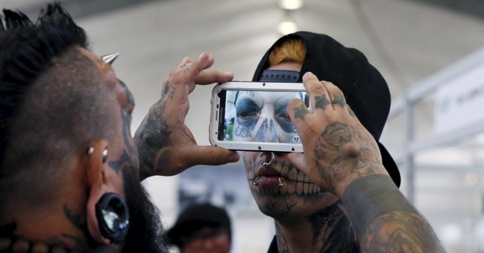 10.nov.2015 - Tatuador venezuelano Emilio Gonzalez (à esq.) fotografa olhos tatuados do jovem Eduardo Henriquez, 19, durante a convenção de tatuagens e suspensão corporal na cidade de Valparaíso, no Chile