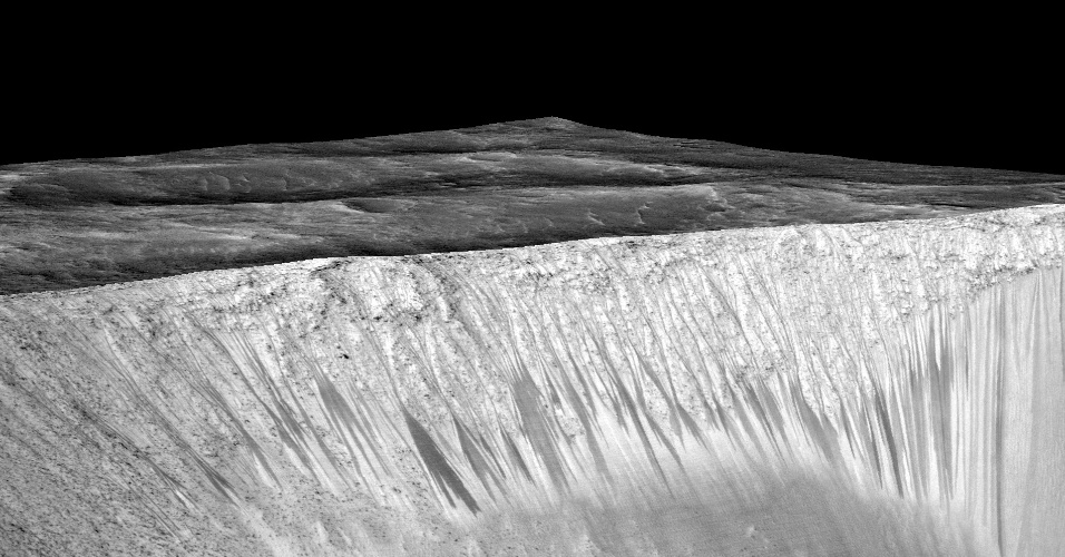 28.set.2015 - Nesta imagem divulgada pela Nasa é possível ver as listras estreitas e escuras, onde os cientistas acreditam que a água em estado líquido flui atualmente