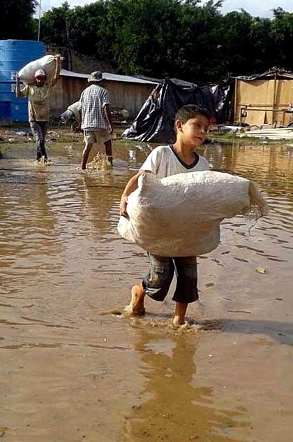 24.dez.2015 - Menino ajuda a salvar objetos após a inundação que atingiu a capital do Paraguai, Assunção, e deixou mais de 130 mil desabrigados. Por conta das fortes chuvas, o país tem sofrido com as cheias do rio Paraguai desde o início do mês de dezembro